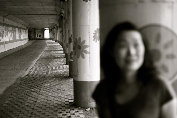 Borroso retrato en blanco y negro de una niña de pie contra una columna de piedra