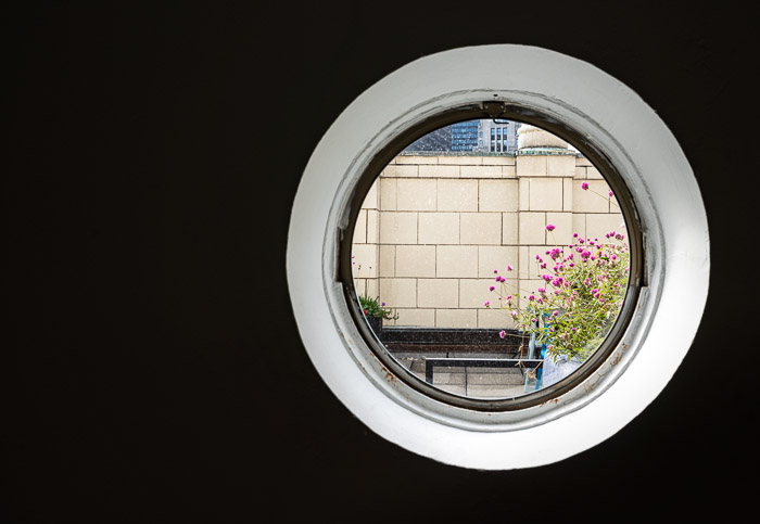 a brick wall seen through a porthole window as an aperture camera metaphor