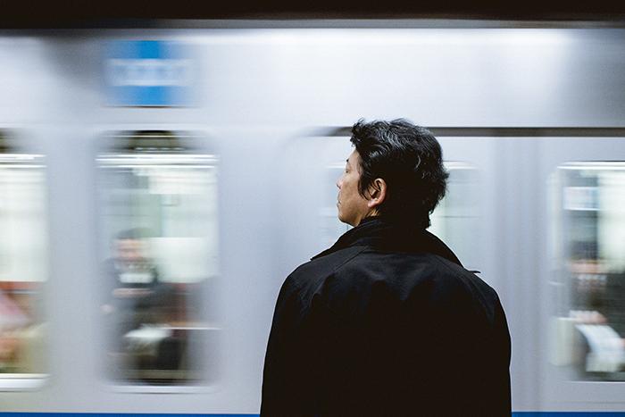 a Japanese man waiting for a train