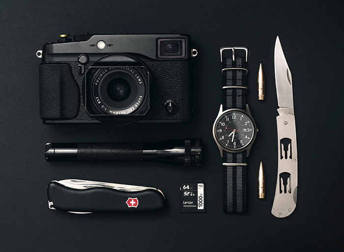 Product photo of a camera, a watch, and pocket knives