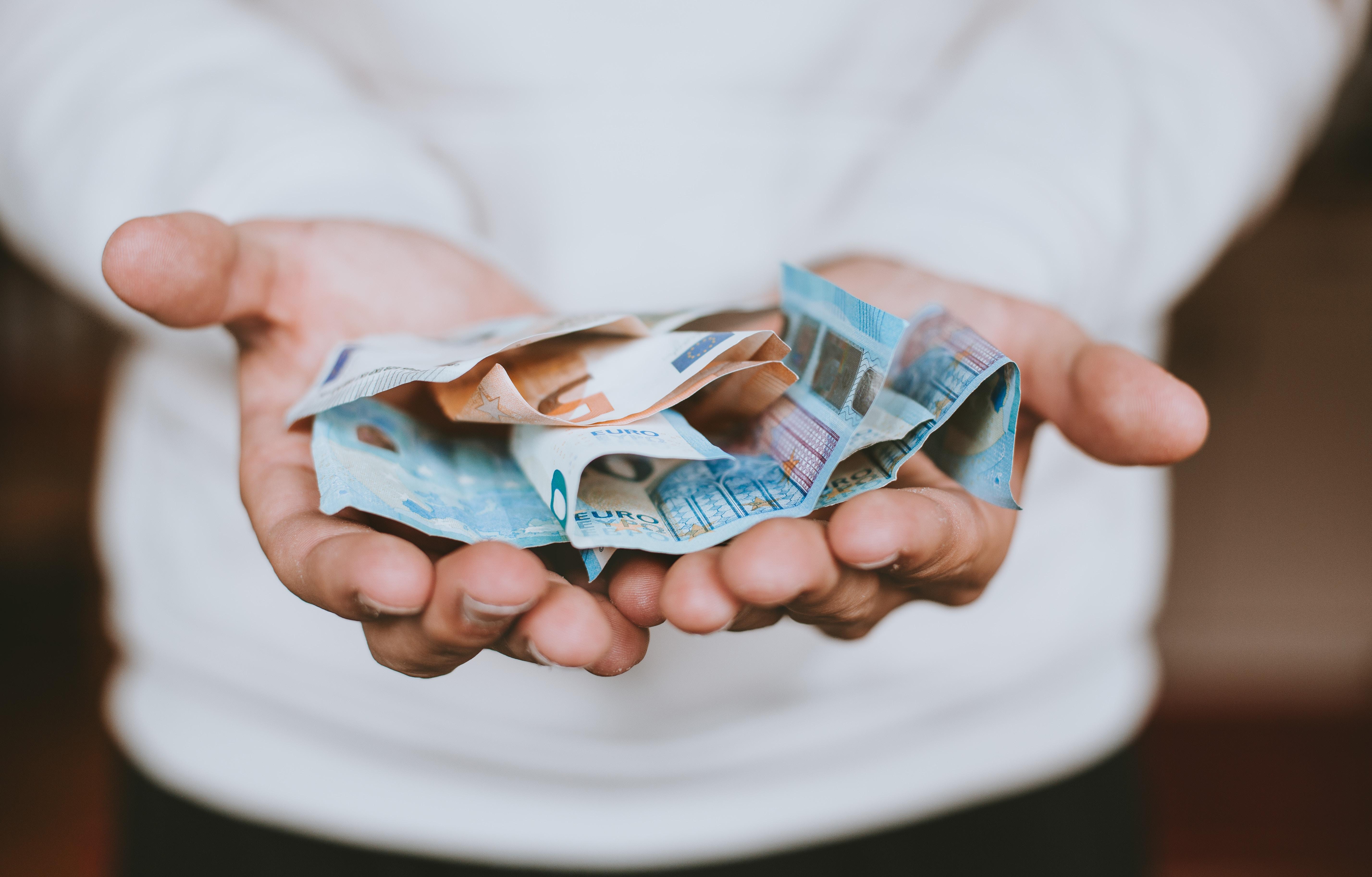 Photo of hands holding euro bills