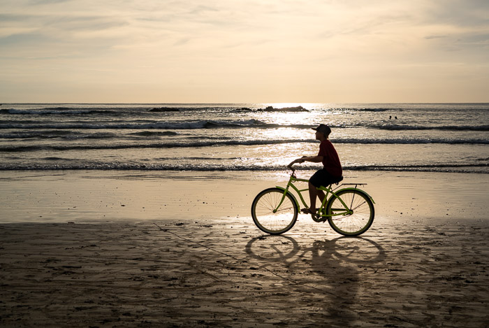 Silhouette of a guy riding a bike on the beach