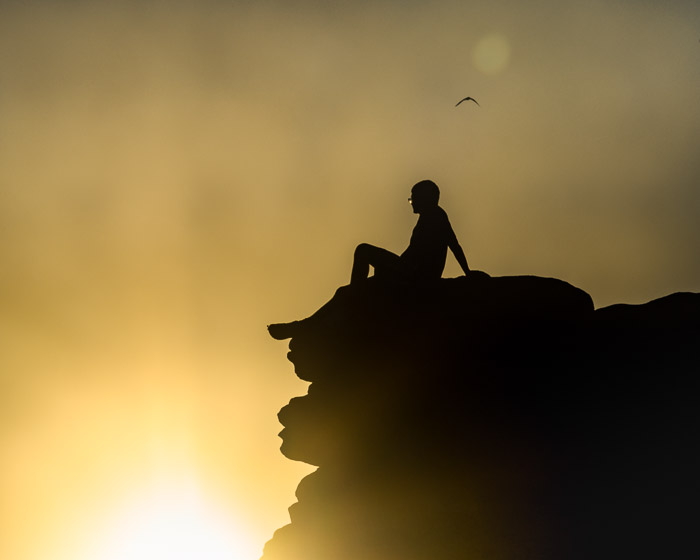 Silhouette of a boy sitting on the edge of a cliff