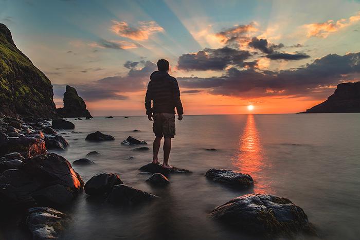 A man watching a sunset on a rocky beach