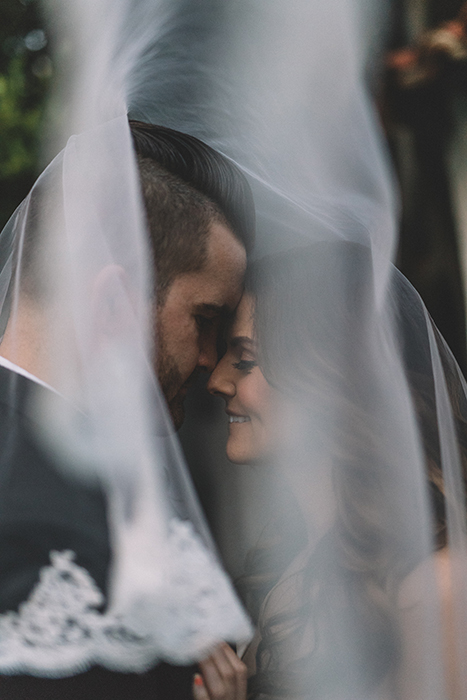 A bride and groom behind a wedding veil