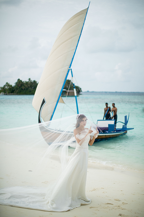 A bride posing with a boat in the background
