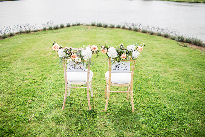 Two chairs on a river bank decorated for the bride and groom