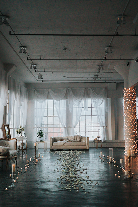 A path of petals and candles leading to a sofa in a loft