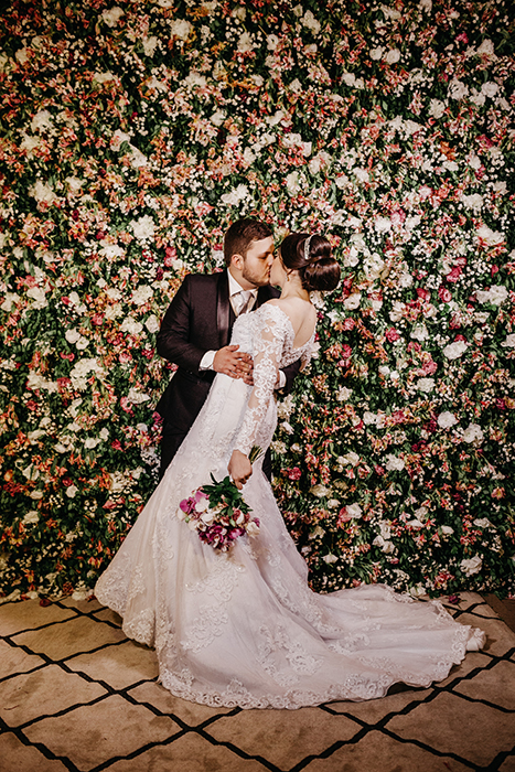 A bride and groom kissing in front of a floral wall