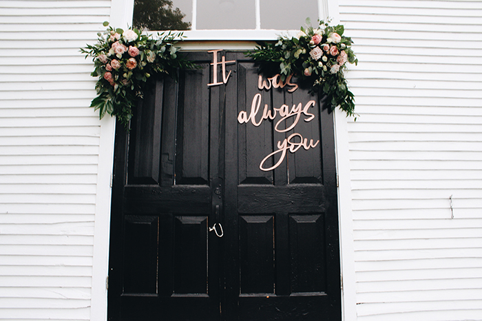 a door decorated with flowers and lettering as wedding photography props