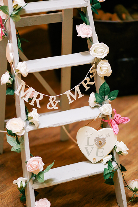 a ladder decorated with flowers and lettering as wedding photography props