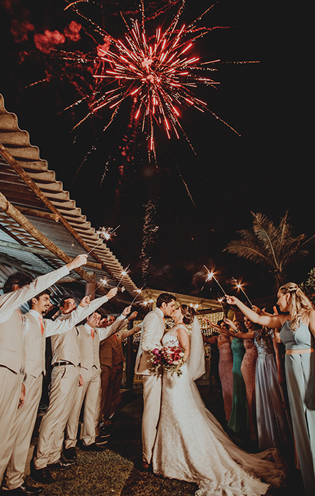 A bride and groom kissing surrounded by sparklers