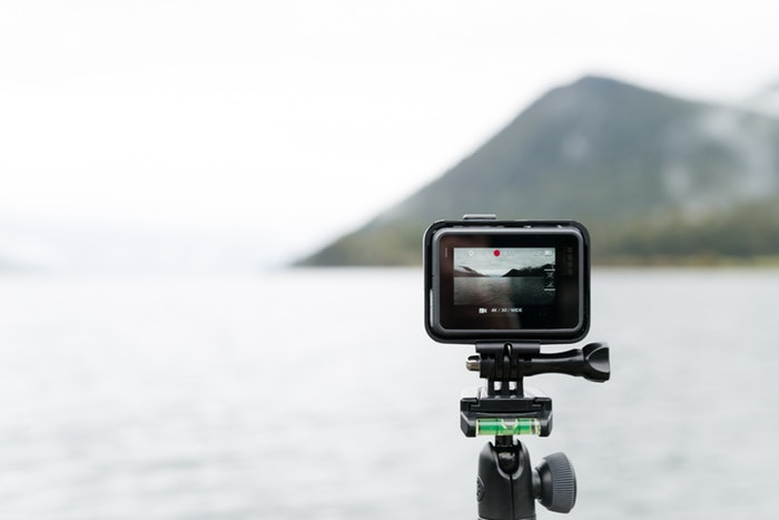 A GoPro on a tripod in front of a lake