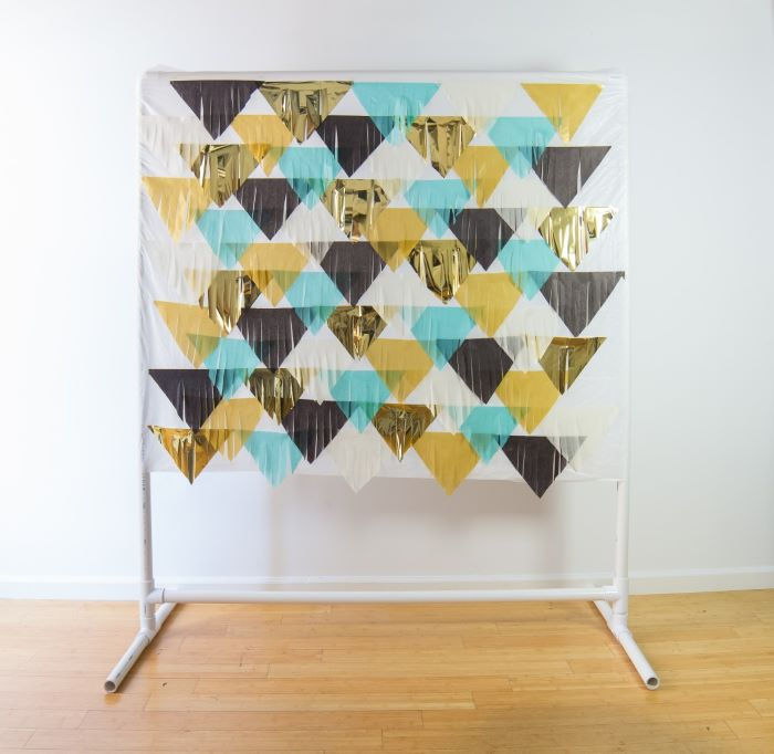 A backdrop stand with a fringed material backdrop