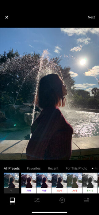 Photo of a woman in front of a fountain