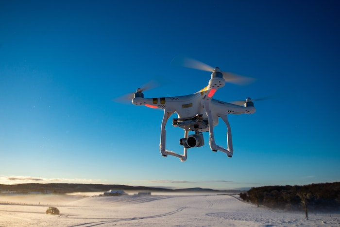 A drone flying above a snowy field