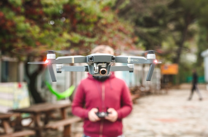 photo of a person flying a drone