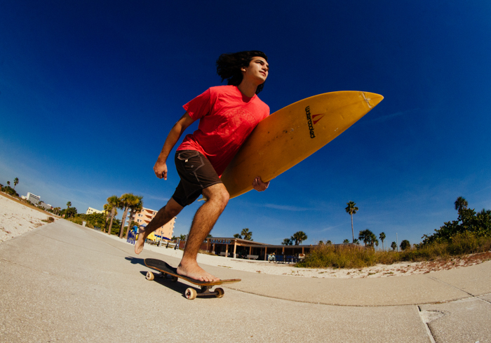 Photo of a guy with a surfboard in his hand on a skateboard