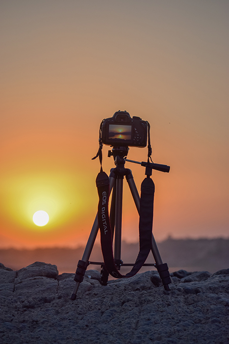 Photo of a camera on a tripod at sunset