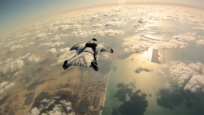 A man flying in a skydiving suit above the clouds