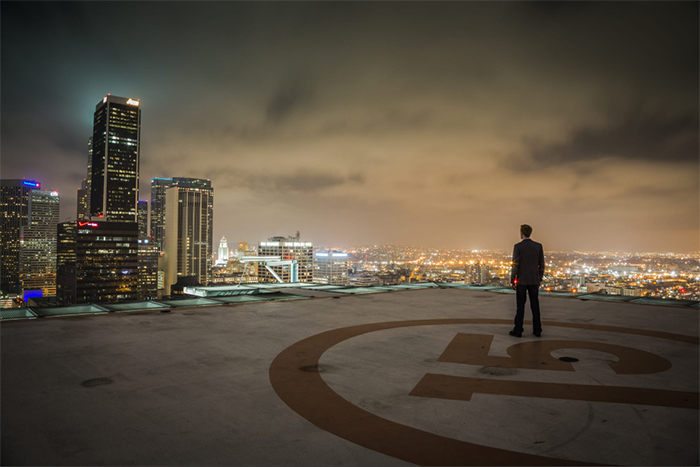 A man standing on the roof of a building with a city skyline in the background