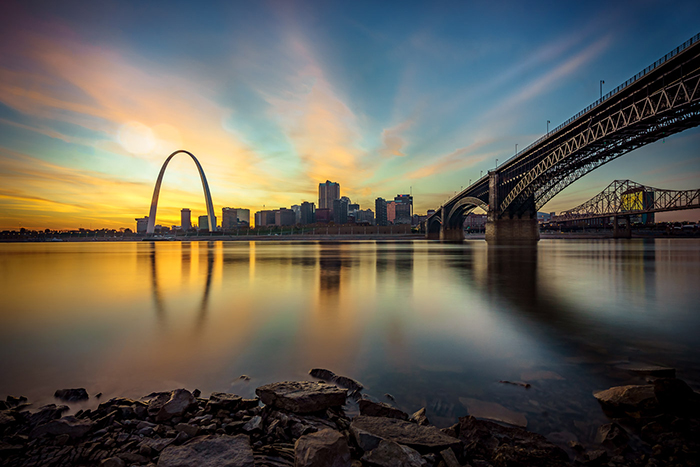 A the cityscape of St. Louis and the Gateway Arch at sunset