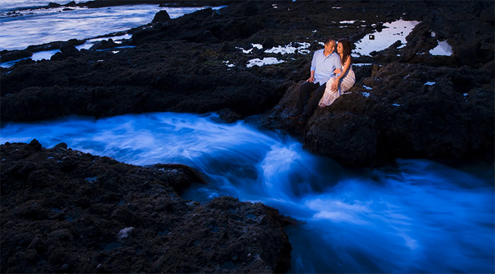 A couple sitting on rocks by rushing water (Screenshot from SLRLounge online photography classes)