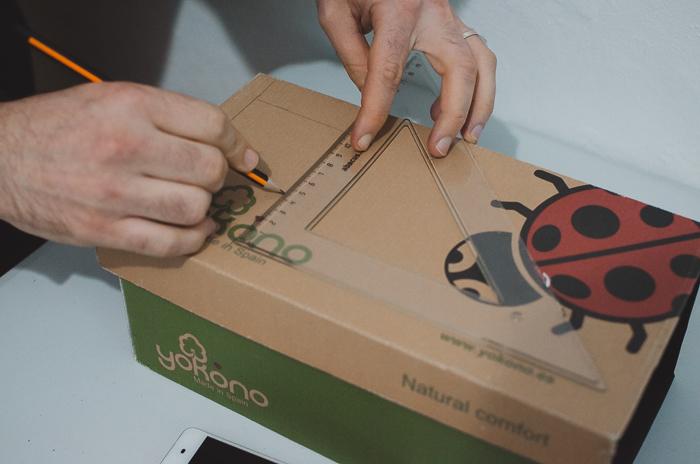 A person measuring a DIY smartphone photo projector