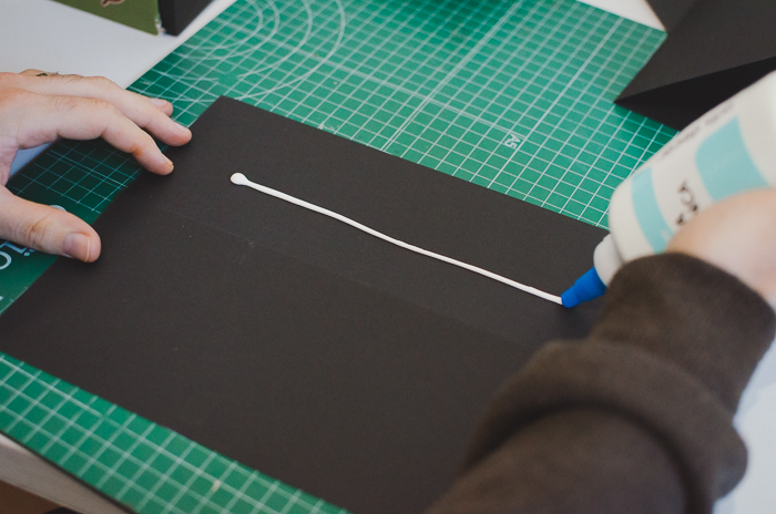 A person gluing black paper to make a DIY projector