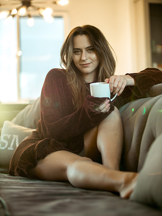 A woman drinking tea on a couch