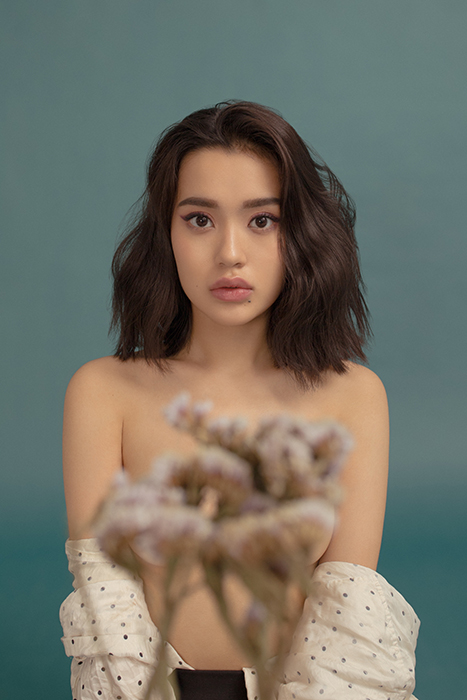 A beautiful girl poses in front of dried flowers