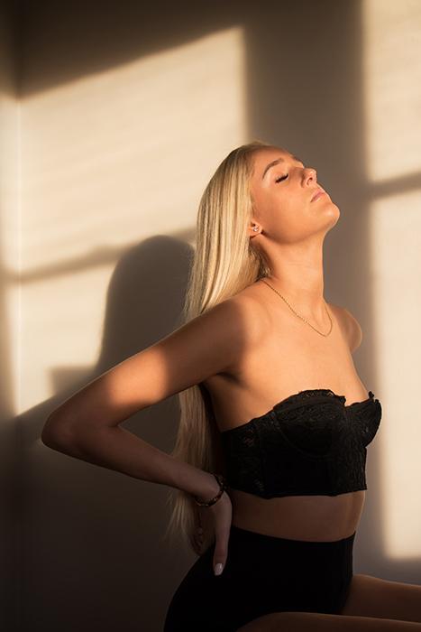 A woman in lingerie posing near a window