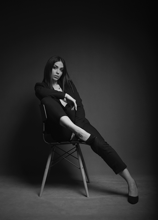 Sensual black and white portrait of a woman sitting on a chair