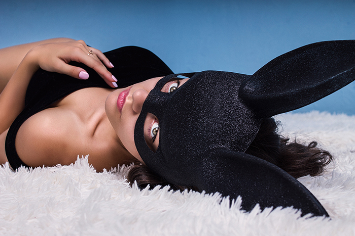 A female in a bunny mask poses on a bed
