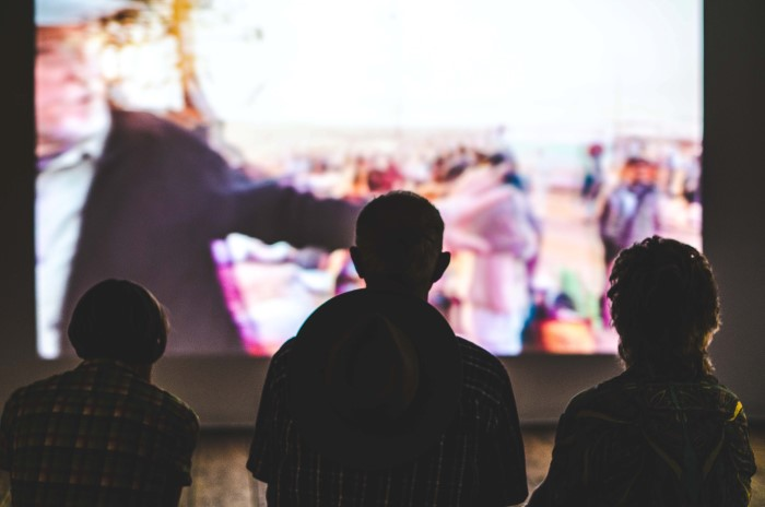 Three people silhouetted against a projected image