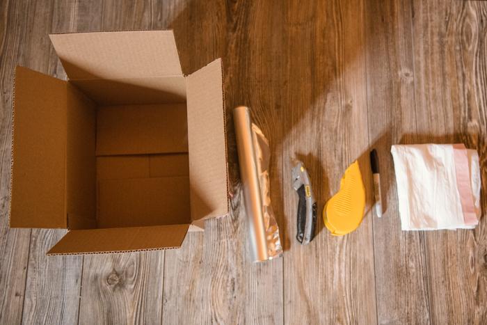 a cardboard box, aluminium foil, cutting knife, tape, stationary