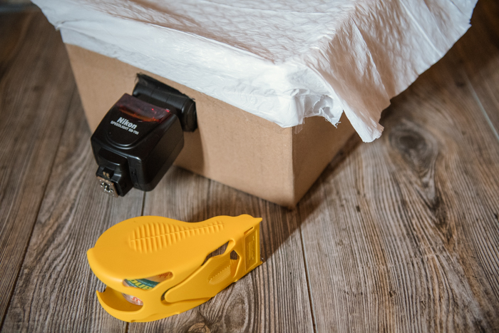 A camera flash inserted into a flap of a cardboard box