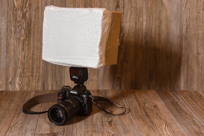 A DSLR below a homemade DIY softbox
