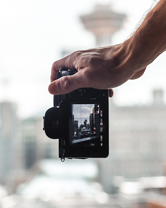 A hand holding a camera and taking dolly zooms of a cityscape