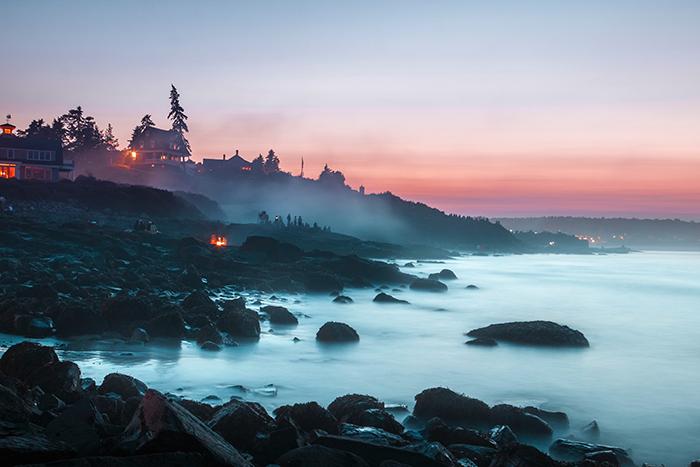 A misty coastal landscape at sunset