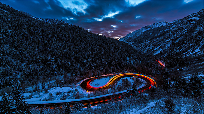 Mountainous landscape with colorful light trails of passing cars shot with long exposure