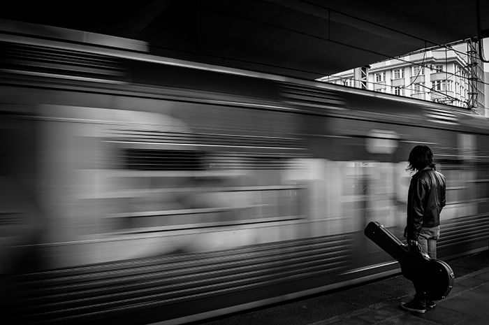 a person with guitar case standing by a moving train