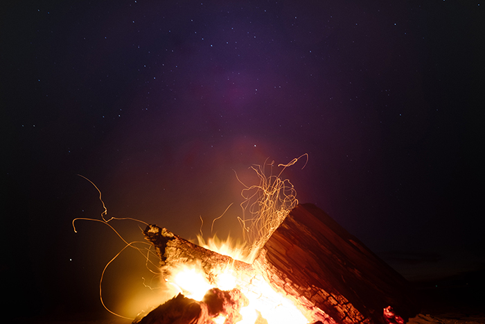 A campfire outdoors under the night sky