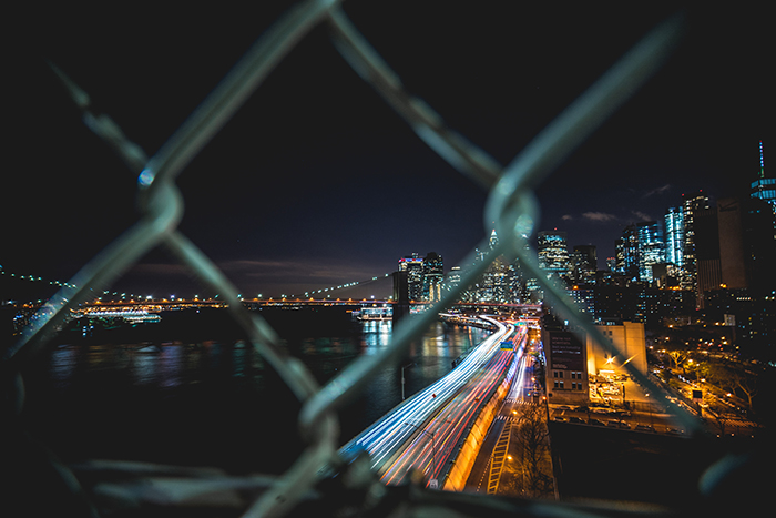 Night cityscape shot through a chain link fence