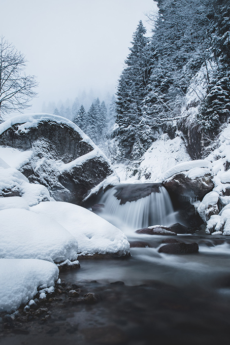 A waterfall among a snowy landscape