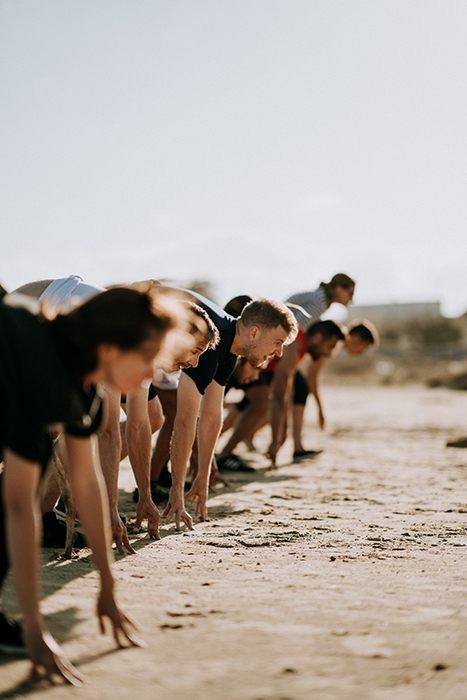A line of people working out on the beach