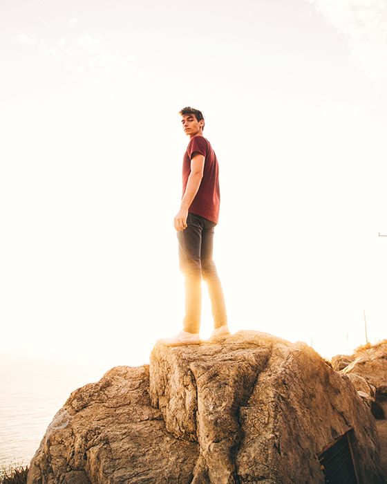 Man posing on a cliff during golden hour lights.