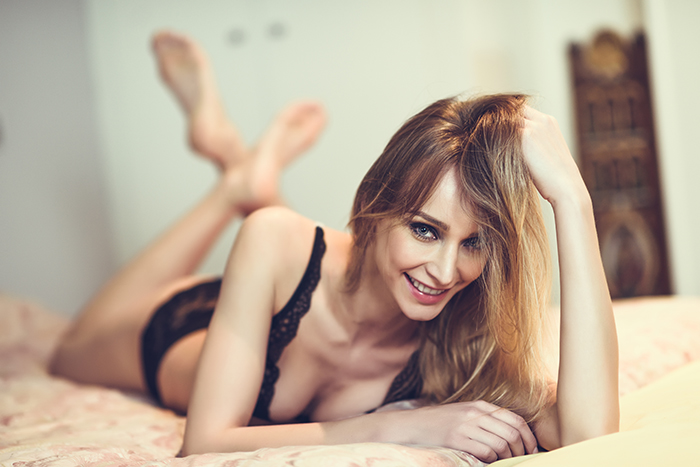 Attractive blonde woman in black lingerie posing on her bed while pushing her hair upward.