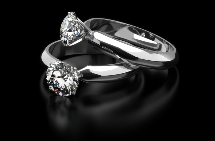 Jewelry product photo of two diamond engagement rings on black background
