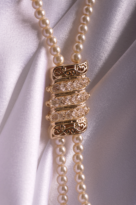 pearl necklace on silk background with a golden medal